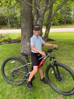 Grade 6 student Colin Joseph MacCormac sitting on his bike outdoors